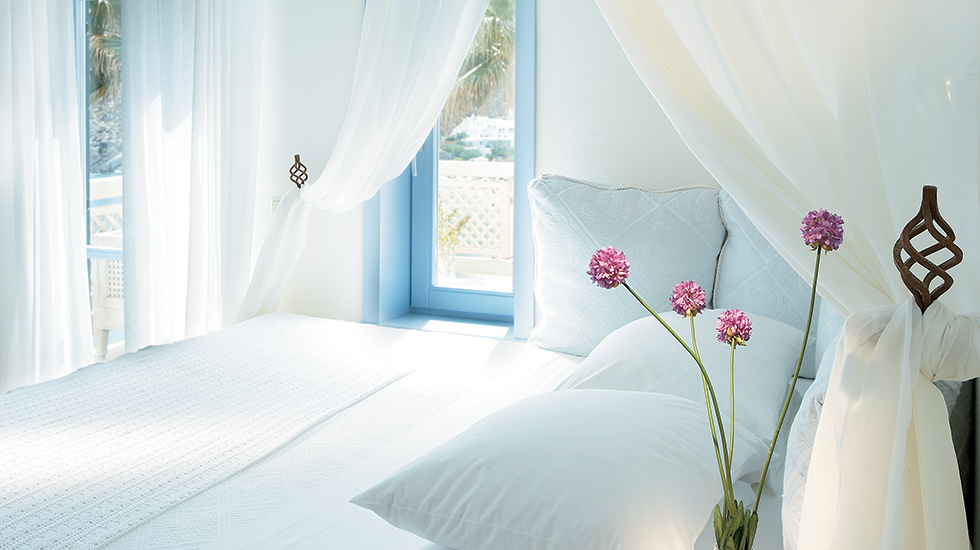 Mykonos Blu Apartment | Master Bedroom with hand-sculpted light fixtures
